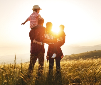 A family standing on a hill facing the sun